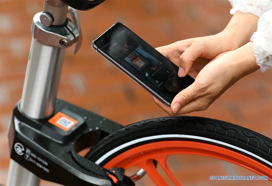 SAPPORO, agosto 22, 2017 (Xinhua) -- Una mujer utiliza su teléfono celular para desbloquear una bicicleta compartida en Sapporo, Japón, el 22 de agosto de 2017. Mobike, una de las mayores compañías de bicicletas compartidas de China, comenzó a funcionar el martes en Japón. (Xinhua/Hua Yi)