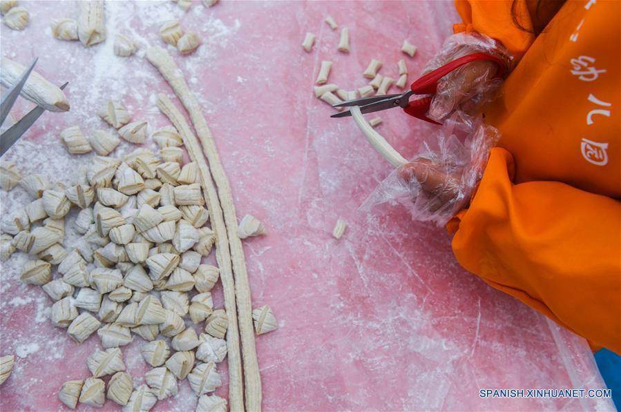 """ZHEJIANG, diciembre 7, 2017 (Xinhua) -- Una niña aprende a elaborar azúcar de malta, un bocadillo tradicional local, en ocasión del """"Daxue"""", el veintiuno de los Veinticuatro Términos Solares, en el Jardín de Niños Central, en el municipio de Huaikan del condado de Changxing, provincia de Zhejiang, en el este de China, el 7 de diciembre de 2017. (Xinhua/Xu Yu)"""