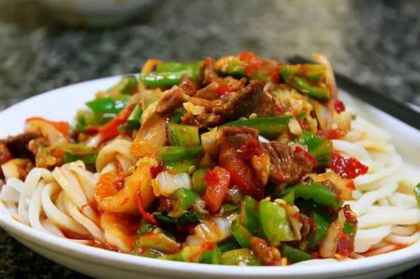 fideos fritos con apio, ajo, tomate, carne de cordero y pimiento
