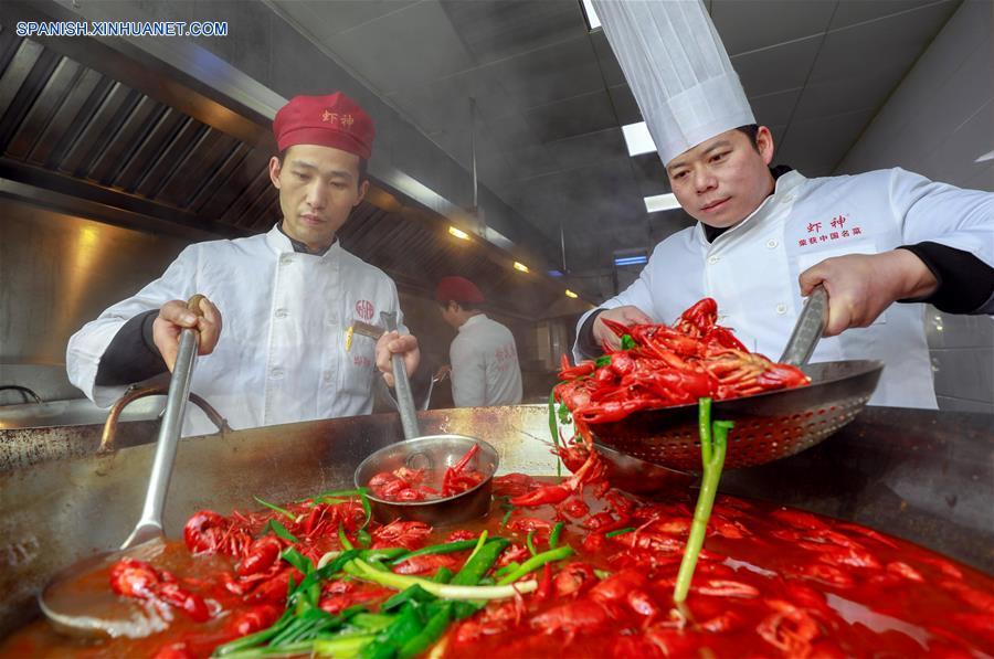 JIANGSU, enero 23, 2018 (Xinhua) -- Chefs cocinan cangrejos de río en un restaunante, en el condado de Xuyi de Huai'an, provincia de Jiangsu, en el este de China, el 23 de enero de 2018. El cangrejo de río es la famosa especialidad del condado de Xuyi y la demanda de cangrejos aumenta a medida que el Festival de Primavera se acerca. (Xinhua/Zhou Haijun)
