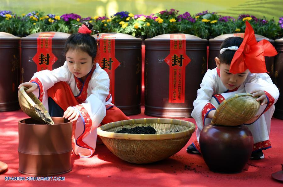BEIJING, mayo 3, 2018 (Xinhua) -- Dos niños portando vestimentas clásicas chinas colocan hojas de té negro Anhua en urnas de cerámica durante una ceremonia tradicional de preservación del té llevada a cabo en el Templo Xiangjie del Parque Badachu, en Beijing, capital de China, el 3 de mayo de 2018. La ceremonia de preservación del té ha sido parte de la cultura china del té. En tal ceremonia, las hojas de té son colocadas en urnas de cerámica antes de ser selladas para su preservación. (Xinhua/Li Jundong)