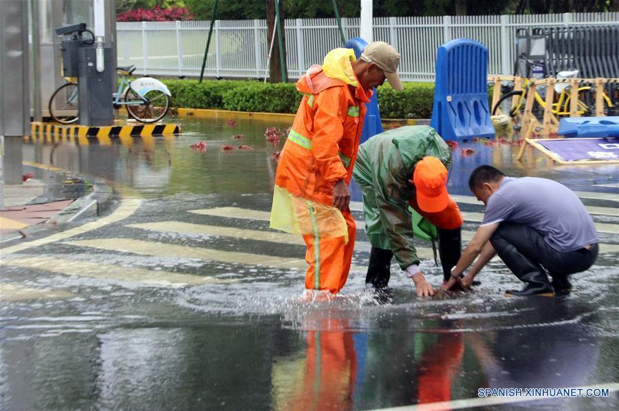 Personas limpian la alcantarilla para drenar el agua de la inundación en Xiamen, en la provincia de Fujian, en el sureste de China, el 7 de mayo de 2018. La zona registró inundaciones repentinas debido a las fuertes lluvias. (Xinhua/Zeng Demeng)