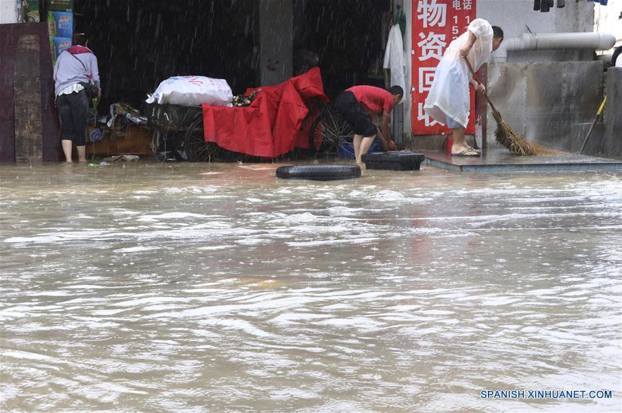 Personas drenan agua de la inundación en Xiamen, en la provincia de Fujian, en el sureste de China, el 7 de mayo de 2018. La zona registró inundaciones repentinas debido a las fuertes lluvias. (Xinhua/Zeng Demeng)