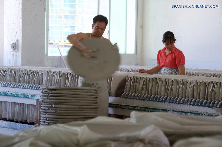 FUJIAN, mayo 17, 2018 (Xinhua) -- Imagen del 15 de mayo de 2018 de un empleado llevando materiales de arcilla en una empresa, en el condado de Dehua de Quanzhou, provincia de Fujian, en el sureste de China. Dehua, es base de la famosa cerámica de China, tiene unas 2,600 empresas de cerámica y más de 100,000 empleados relacionados. El condado ha promovido el horno eléctrico para proteger el medio ambiente y elevó toda la cadena industrial de la cerámica. En 2017, el valor de salida de la industria de la cerámica en Dehua alcanzó los 3.58 millones de dólares estadounidenses. (Xinhua/Zhang Chuanqi)