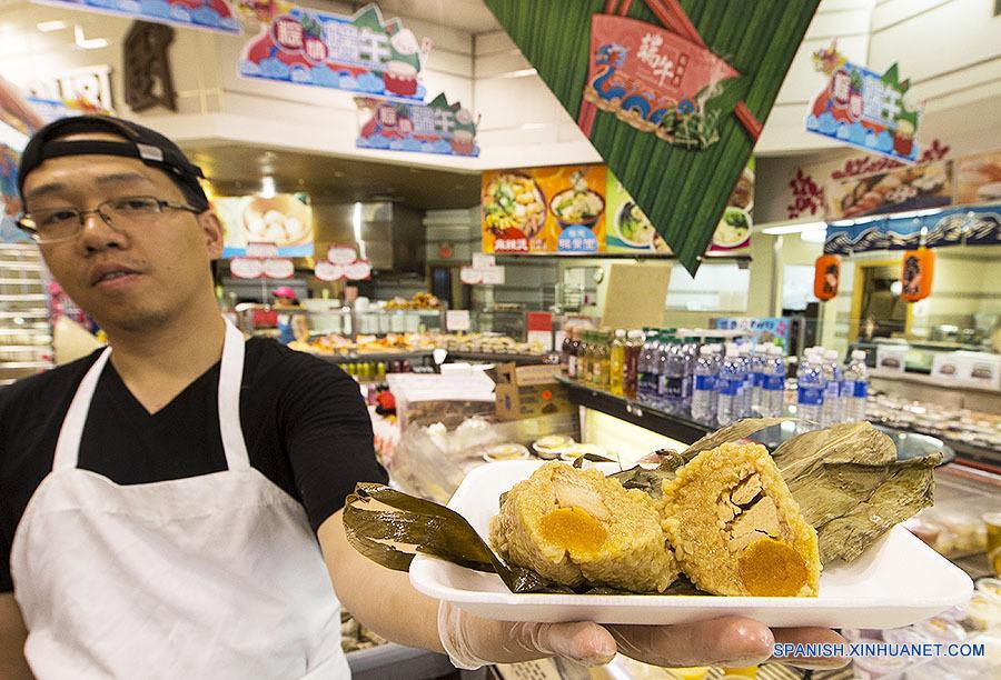 """新华社照片,多伦多,2018年6月18日 (国际)(3)多伦多端午""""味""""足 6月17日,在加拿大多伦多一家超市,店员展示一款颇受欢迎的蛋黄肉粽。 端午节期间,多伦多的许多华人超市推出粽子专柜,提供各种口味、数量充足的粽子,吸引顾客。 新华社发(邹峥摄)"""