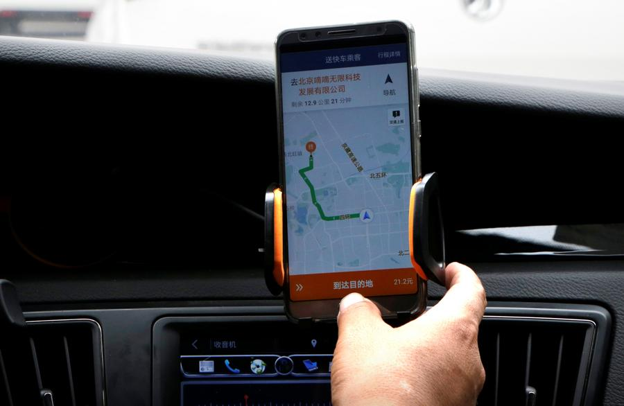 A Didi Chuxing driver checks the information on the application in his car in Beijing, China August 28, 2018. REUTERS/Jason Lee