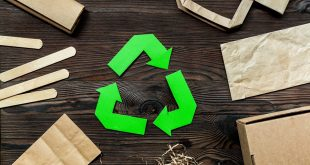 Paper recycle sign with paper and carton garbage on wooden background top view.