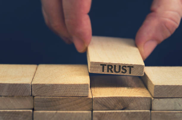 Trust word written on wooden block. Building trust business concept.